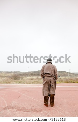 Lonely senior man with raincoat and hat standing on road on cloudy day.