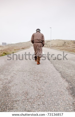 Lonely senior man with raincoat and hat walking on road. Lost.