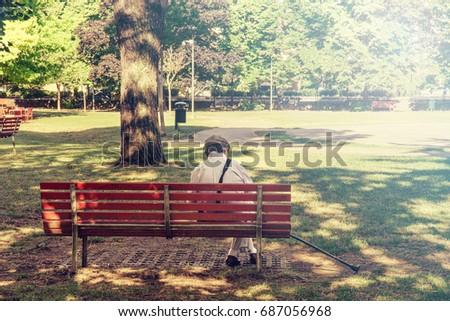 lonely senior sitting on a bench, he is alone at the park