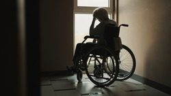 lonely senior woman looking through the window of the nursing home. Mental health affected during the quarantine. High quality photo