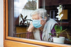 lonely senior woman with surgical mask sitting on a window plane at home, coronavirus and covid-19 provisions