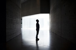 Lonely silhouette in dark architecture with light background. Horizontal Image. Full body of man in profile. Mystery photo.