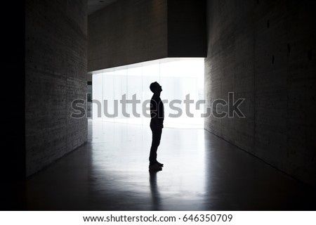 Lonely silhouette in dark architecture with light background. Horizontal Image. Full body of man in profile. Mystery photo. #646350709