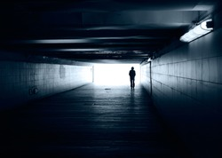 Lonely silhouette in dark subway tunnel goes towards the light