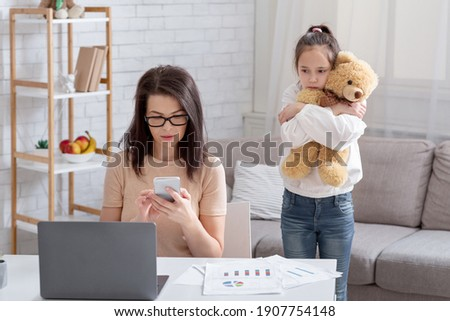 Lonely teen girl hugging teddy bear while her busy mom working online from home, not paying attention to child. Depressed kid feeling neglected, missing her parent. Covid-19 quarantine family problems Stock photo ©