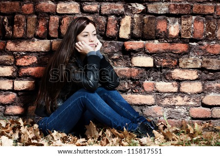 Lonely teenage girl sitting on the ground,a sad expression, leaning on an old brick wall.