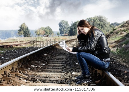 Lonely teenager sitting on the track and read the letter.