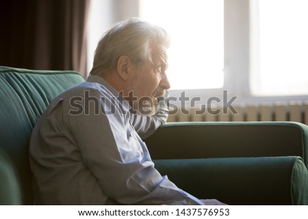 Lonely thoughtful senior old grandpa sit alone on sofa thinking of loneliness problems, pensive melancholic elder retired man looking at window feeling depressed anxious worried lost in thoughts