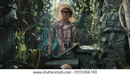 Lonely tourist lost in the jungle, she is scared and holding a map Photo stock ©