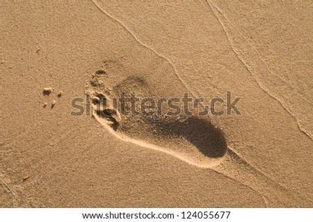 Lonely trace from a bare foot on sand.