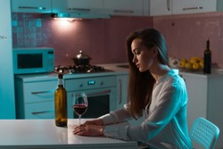 Lonely, unhappy, sad beautiful young woman in a blouse with glass of red wine is drinking alone in evening at home. Female alcoholism and alcohol addiction
