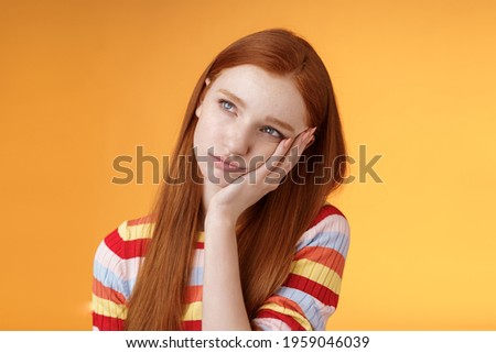 Lonely upset moody cute redhead girlfriend feeling boredom leaning palm look up pouting frowning displeased standing uneasy attend boring meeting, staring uninterested reluctant orange background Stock photo ©