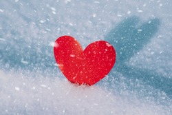 Lonely valentine. Red heart in cold, frosty morning snow. Valentine's Day greeting card. A symbol of love and romantic relationships. Congratulations on holiday of February 14