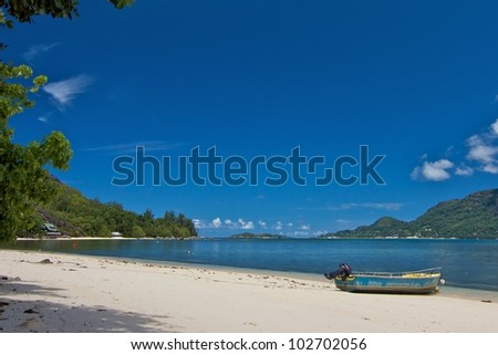 Lonely white beach with a motor boat and the lush green forests and blue waters of the Indian Ocean on Cerf island, Seychelles - stock photo