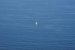 Lonely white sailing boat in the middle of a calm sea. The whiteness of the ship contrasts with the blue of the sea. Copy space. Horizontal photography.