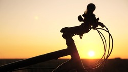 lonely woman cyclist resting in park. Hiker healthy young woman stands on hill next to bicycle, enjoying nature and sun. Free girl travels with bicycle at sunset. concept of adventure and travel.