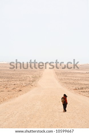 Lonely woman is walking on the desert road