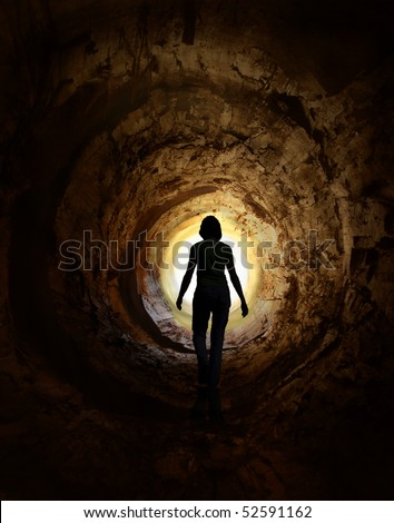 Lonely woman is walking through dark tunnel to the light