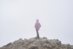 Lonely woman on the edge of a cliff looking into the void on a gray day.