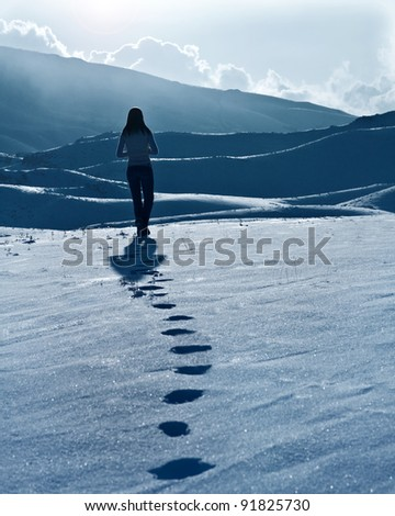 Lonely woman silhouette at winter mountains, footprints on the snow, enjoying wintertime nature view,one girl walking outdoor
