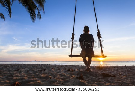 Lonely woman sitting on a rope swing at sunset watching at the sea and thinking about life #355086263