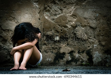 Lonely woman sitting on the floor near old wall vintage tone,sad depression, violence, bipolar concept, hard contrast,soft focus #690344611