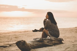 Lonely woman sitting On the sand sunset.are Lonely. style abstract Vintage tone