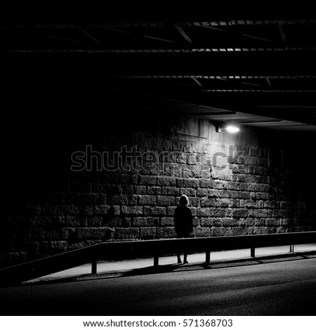 Lonely woman standing in a night tunnel #571368703