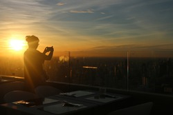 Lonely woman taking photo of sunrise on high rise building in  Thailand.
