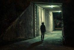 Lonely woman walking in a dramatic mystic dark alley at night. Danger and scary concept.