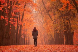 Lonely woman walking in park on a foggy autumn day. Lonely woman enjoying nature landscape in autumn. Autumn day. Girl sitting on grass Color vertical image.