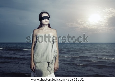 Lonely woman with blindfold listening waves of the sea during sunset. Special colors and processing in artistic manner #50961331