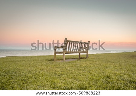 Lonely wooden sitting bench with beautiful sunset sky in the background and peaceful ocean water. Bench founded in memory of wonderful grandfather who passed away.   Foto stock ©
