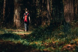 Lonely young girl with backpack goes along picturesque path into dark forest. Female teenager wandering in woods or lost. Free life of youth, independence or freedom of choice. Run away from home
