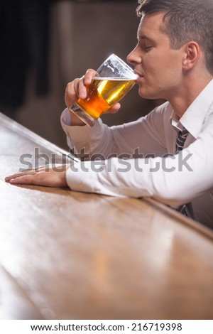 Lonely young man drinking alone at the pub. man sitting at end of bar counter sipping pint of draught beer