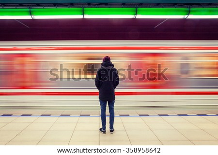 Lonely young man shot from behind at subway station with blurry moving train in background #358958642