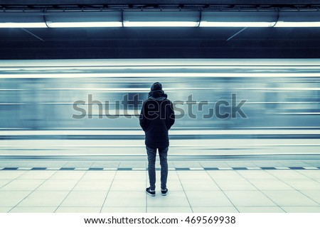 Lonely young man shot from behind at subway station with blurry moving train in background #469569938
