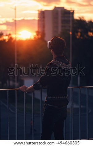 lonely young man trying a pair of VR glasses raising one hand dressed in a cool sweater and trendy outfit excited by augmented reality sunlit by an amazing sunset from background low light soft focus