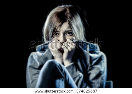 lonely young teenager girl in stress and pain suffering depression looking sad and scared with fear face expression isolated on black background victim of abuse or in mental condition