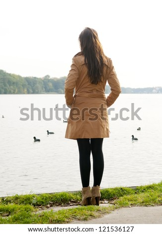 lonely young woman on lake, rear view