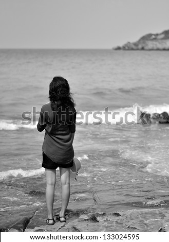 Lonely young woman on the beach, in black and white