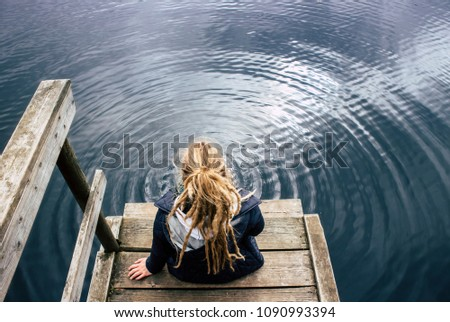Lonely young woman sitting by the lake water and causing ripples pattern on a blue lake water. She has all the time in the world concept.