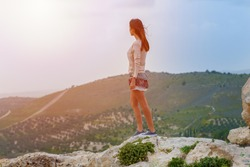 Lonely Young Woman stands dangerously close to edge of cliff top above wild nature wood on the mountain.  Long Hair blowing in the wind.