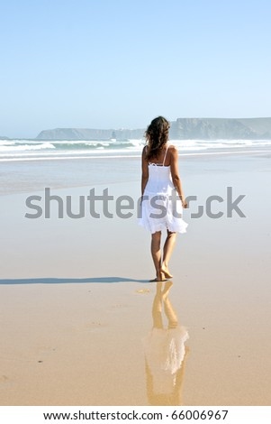 Lonely young woman walking on the beach