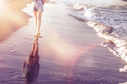 Lonely young woman walks on an empty wild beach. Sea shore with girl walking through waves. View from back. Summer holidays vacation travel concept. Copy space.