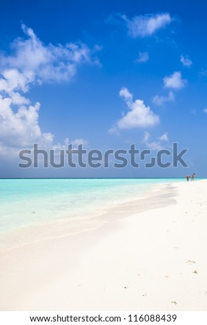 lonesome beach with blue sky, white clouds and turquoise sea