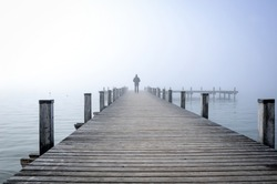 Lonesome figure on old wooden jetty by the lakeside