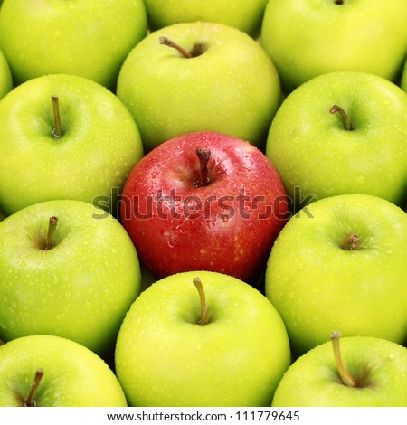Lonesome red apple in a pile of green apples