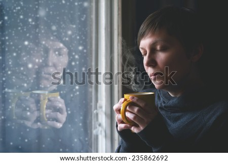 Lonesome woman drinking cup of coffee by the window of her living room while the snow is falling outside. Selective focus with shallow depth of field.
