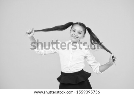 Long and healthy. Cute small schoolgirl holding long hair ponytails on yellow background. Adorable little child in formal wear being proud of long hair. Styling long hair for school.